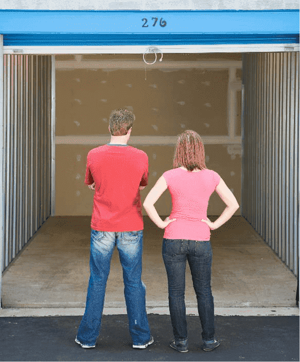 Couple is standing in front of an empty storage unit deciding how to organize it